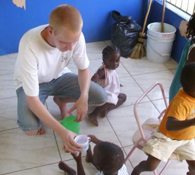 자메이카 치의학 프로젝트 봉사자가 아이 식사를 돕고있다.