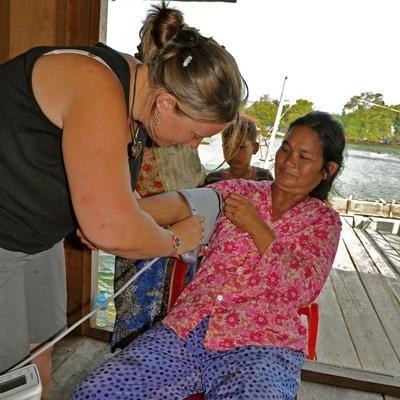 캄보디아 의료 프로젝트 봉사자가 한 여성의 혈압을 재고 있다
