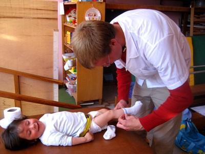 페루 간호 프로젝트 봉사자가 어린이 상처 소독을 해 주고 있다