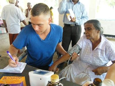스리랑카 의료 봉사에서 여성의 혈압을 기록하는 간호 봉사자