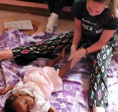 케냐 작업치료 프로젝트 인턴이 여자 어린이의 다리 운동을 돕고있다
