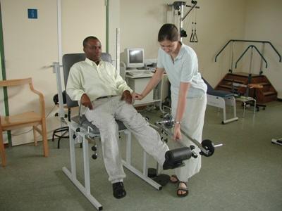 가나 병원에서 환자의 다리를 치료하고 있는 물리치료 인턴