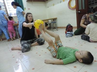 한 어린이가 베트남 물리치료 프로젝트 봉사자의 치료를 받고 있다