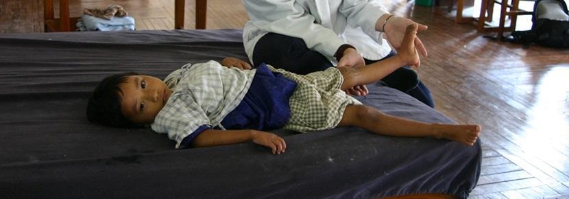 해외 자원 봉사 물리치료 프로젝트 봉사자가 어린이를 치료하고 있다