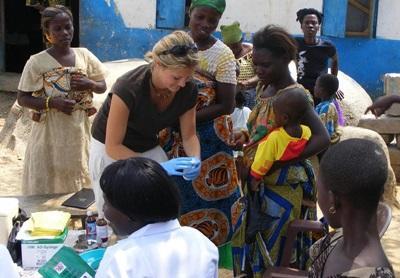 가나 공중보건 프로젝트 봉사자가 마을 어린이들 검진을 하고 있다