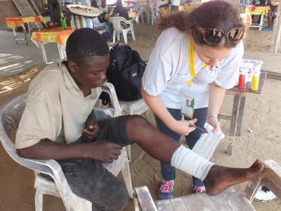 토고 프로젝트 인턴이 환자를 치료하고 상처를 붕대로 감아주고 있다