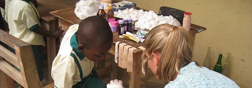 공중보건 프로젝트 봉사자가 어린이의 상처를 치료해 주고 있다