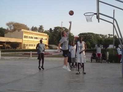 Volunteer demonstrating basketball skills to students on the Sports Project in Senegal