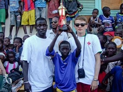 Student wins a basketball tournament trophy with his volunteer coach on the Sports project in Senegal