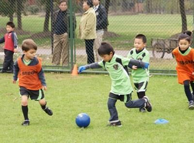 중국에서 봉사 코치와 축구를 하고 있는 학생들