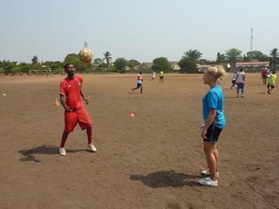 가나에서 여성 봉사자가 청년 축구팀을 코치하고 있다