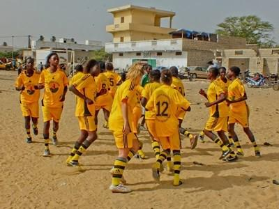 Students on the football team in Senegal warm up before a game
