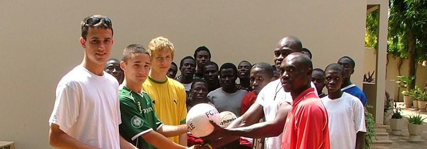 스포츠 프로젝트에 참가한 봉사자가 학교에서 축구를 코치하고 있다