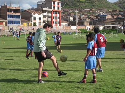 페루의 어린이가 프로젝트어브로드 봉사자에게 축구 지도를 받고 있다.