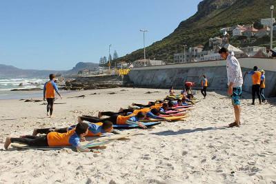 뮈젠버그 해안에서 서핑 교육을 하고 있는 자원봉사자와 어린이들