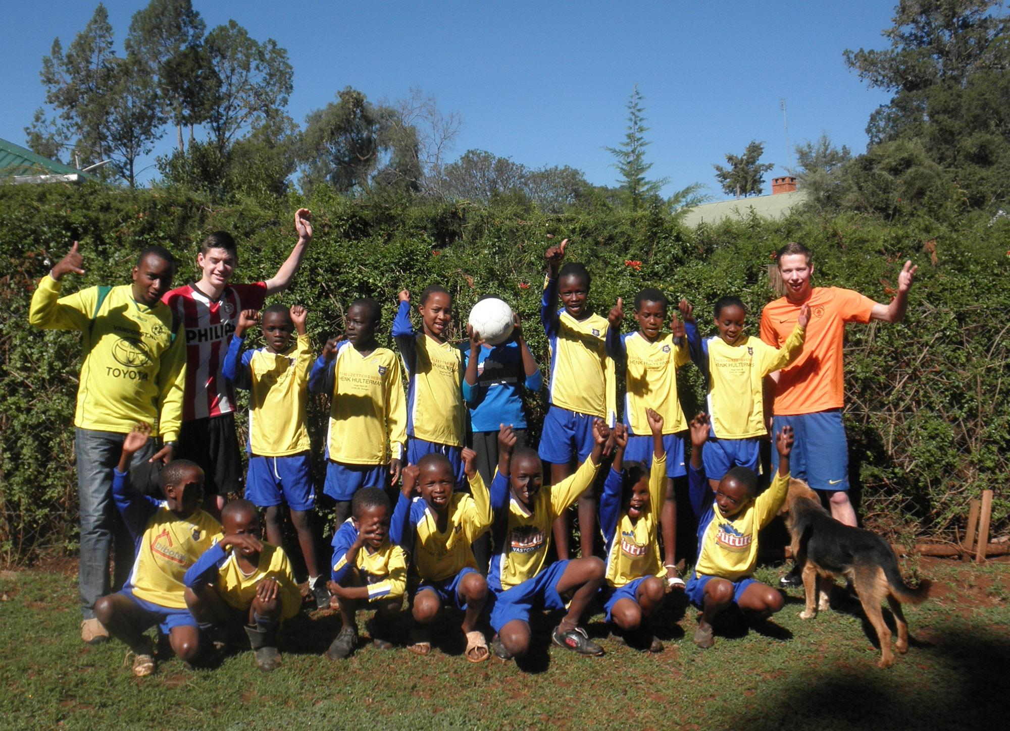 학교 축구팀의 회원들이 봉사자들과 함께 사진을 찍고 있다