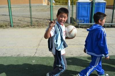 몽골에서 어린 소년이 봉사자와 축구를 하고 있다