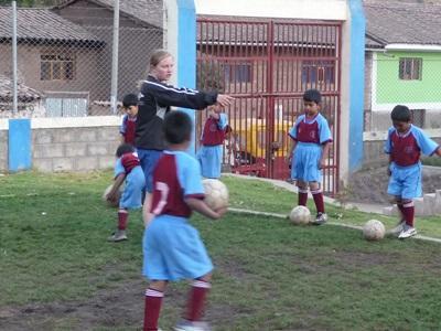 축구 코치 봉사자가 페루 학교의 아이들을 지도하고 있다