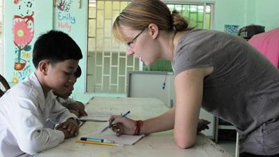 캄보디아의 어린이가 공부를 가르쳐주는 교육봉사자에게 배우고 있다