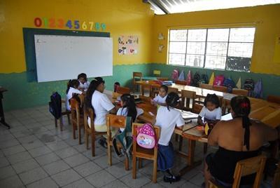 에콰도르의 학교에서 교육봉사자가 내 준 과제를 하고 있는 학생들