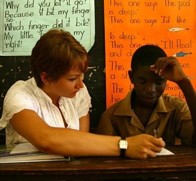 봉사자가 자메이카의 학교에서 학생들에게 개인지도를 하고 있다