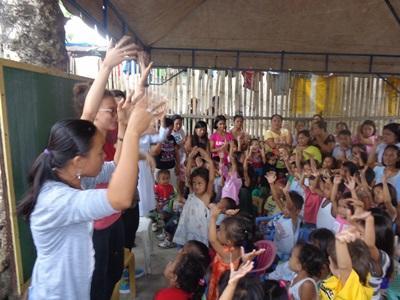 봉사자가 필리핀 학교에서 아이들에게 음악교육을 하고 있다