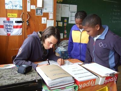 남아공의 학교 교육 프로젝트에 참가한 봉사자가 아이들에게 공부를 가르치고 있다