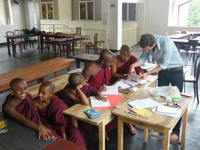 봉사자가 스리랑카의 학교에서 승려 학생들을 가르치고 있다