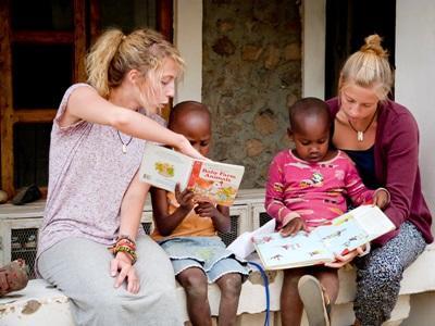 탄자니아의 어린이들이 교육봉사자에게 책읽기를 배우고 있다