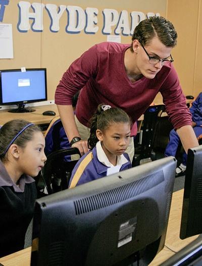 남아공의 학교에서 봉사자가 아이들에게 IT수업을 하고 있다