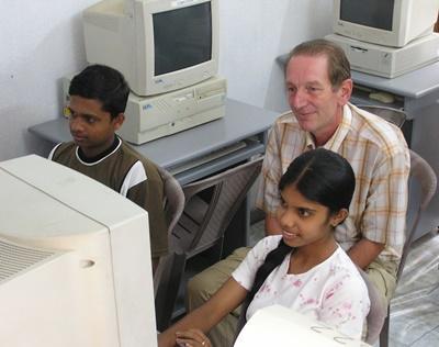 봉사자가 스리랑카의 아이들에게 IT교육을 하고 있다